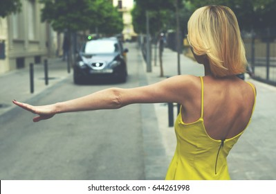 Back view young sexy woman in yellow dress hailing a cab taxi standing on the road with trees, young female tourist with hand gesture stopping taxi in urban setting, businesswoman calling taxi auto