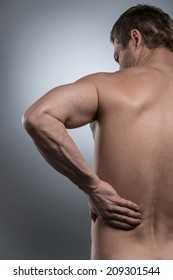 back view of young shirtless man with back pain. young man standing on grey white background