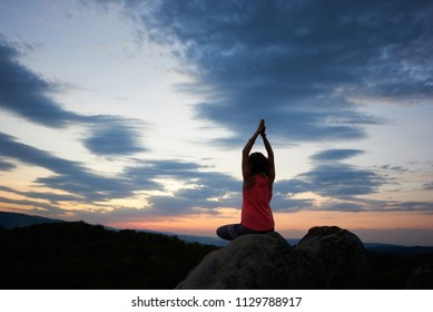Back view of young slim athletic woman sitting on big rock in yoga pose with raised arms on green forest and beautiful sky at sunset background. Meditation and healthy lifestyle concept. Siddhasana