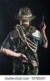 Back view of young soldier in camouflage with guns and rope.