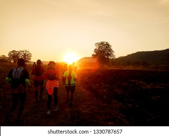 Back view of young sport man runner warm up before running with blurry group of runner and trees background against sunrise morning.