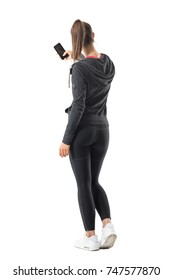 Back view of young sporty fit woman taking photo with smartphone. Full body length portrait isolated on white background.