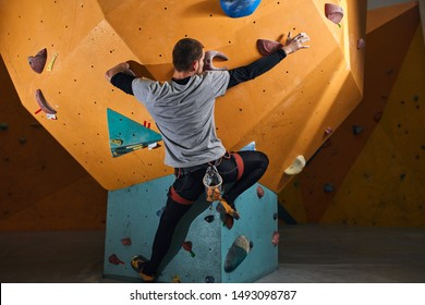 Back view of young strong sportsman without forearm rock climbing, motivated and powerful, overcomes physical disability, doesn't get discouraged, enjoys his active bouldering hobby.
