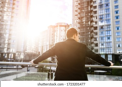 Back view of a young success man in a smart casual jacket, he confidently stands and looks at the city from a top