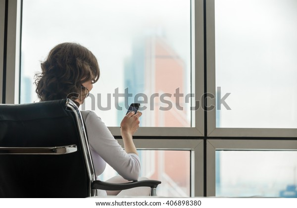 Back view of young successful business lady making call using smart phone. Model sitting in office comfortable armchair at window with beautiful city scenery and looking at cellphone screen. Copyspace
