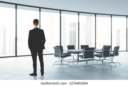Back view at young successful businessman standing in modern office looking through panoramic window at cityscape