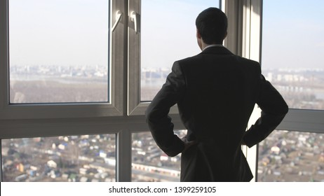 Back view of young successful businessman standing in front of windows looking into distance to the city