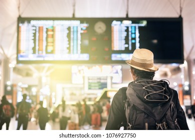 back view of a young traveler or tourist looking at airport time board for flight schedule, travel, holiday, tourism and holiday concept