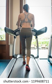 Back view of young woman athlete running on treadmill in gym