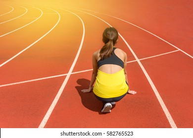 Back view of young woman athlete at starting position ready to start a race. Female sprinter ready for sports exercise on racetrack with sun flare.