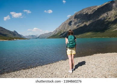 back view of young woman with backpack looking at Gjende lake, Besseggen ridge, Jotunheimen National Park, Norway