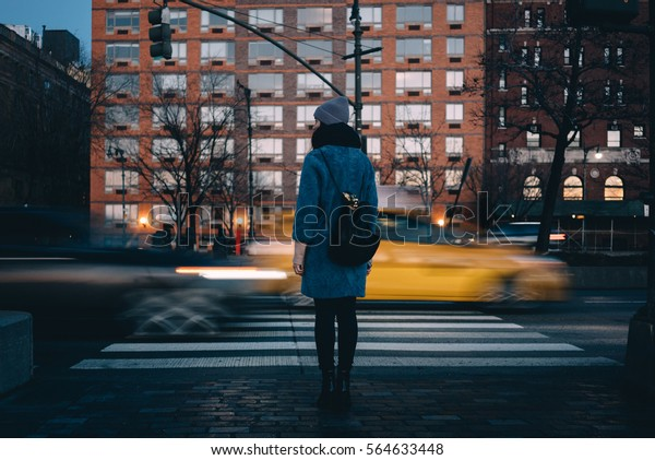 Back view of a young woman with backpack waiting for green traffic light while standing at the Chelsea district, New York City , USA