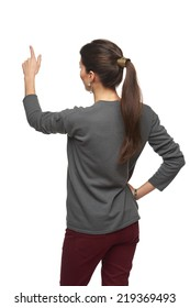 Back view of young woman in cardigan pointing at copy space, isolated on white
