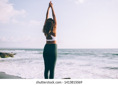 Back view of young woman doing tadasana for relaxes centers attention and sharpens concentration, female enjoying time for practising yoga on coastline training balance and harmony on nature