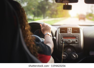 Back view of Young woman driving her car. Driving car at holiday, nature,travel and vacation concept.