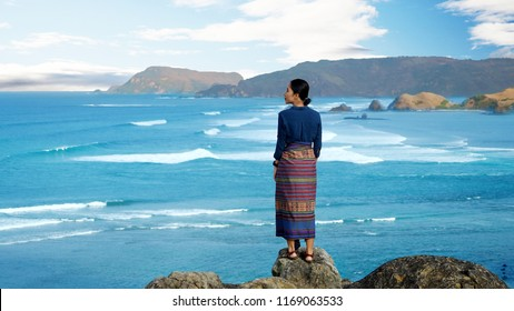 Back view of young woman enjoying seascape while standing on the Merese hill. Shot in Lombok, Indonesia