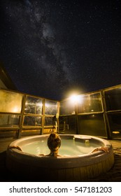 Back view of a young woman enjoying hot tub under the stars and milky way in New Zealand