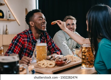 back view of young woman feeding african american man with fried onion ring while celebrating octoberfest in pub