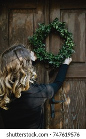 Back view of Young woman hanging a Christmas wreath on her home