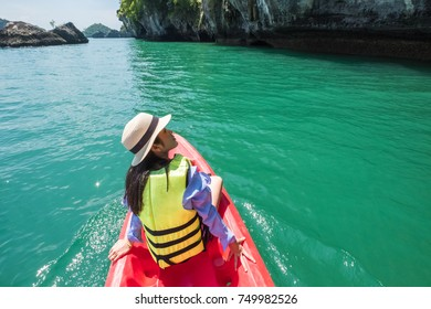 Back view of the young woman in hat relaxing on the boat and looking at the island. Travelling tour in Thailand