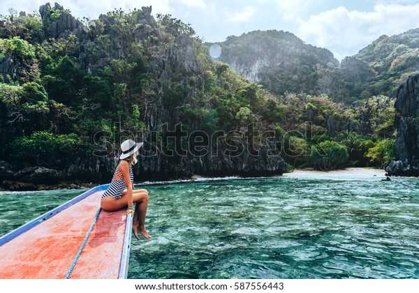 Back view of the young woman in hat relaxing on the boat and looking at the island. Travelling tour in Asia: El Nido, Palawan, Philippines.