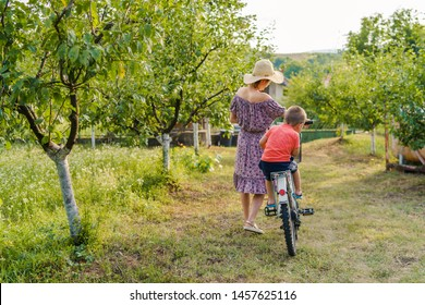 Back view of young woman holding handlebar of the bicycle bike pushing and driving her little small boy son at the gate to the road