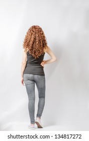 Back view of young woman in jeans and  black shirt walking. Rear view