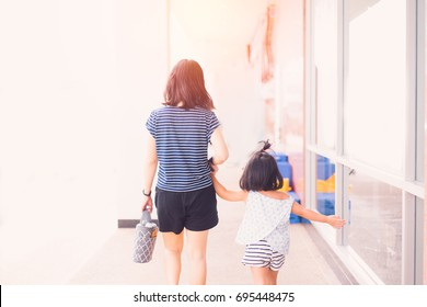 back view of young woman with little girl walking through supermarket.