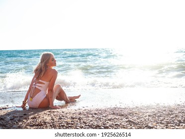 Back view of young woman lying on the beach sand. Sexy woman tans safely on the beach in the setting sun.