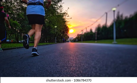 Back view of Young woman and man running on the road in the City green park against sunset sky in evening. Couple or friends jogging in garden evening.
