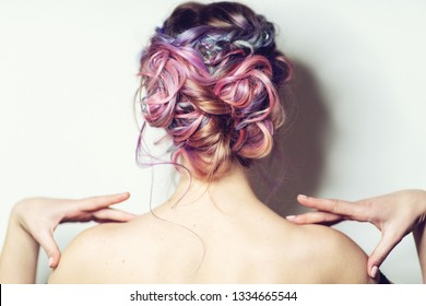 Back view of young woman with modern hairstyle with colorful haircut.