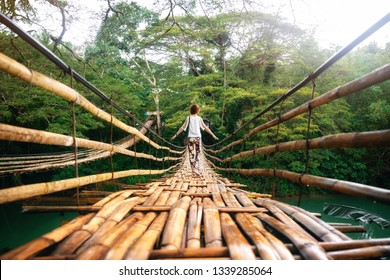 Back view of young woman on suspension wooden bamboo bridge across Loboc river in jungle. Vacation on tropical island. Bohol, Philippines