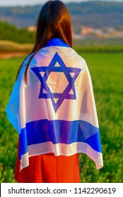 Back view Young woman patriot jewish  girl standing with flag of Israel on amazing landscape in beautiful summer.Memorial day-Yom Hazikaron, Patriotic holiday Independence day Israel - Yom Ha'atzmaut