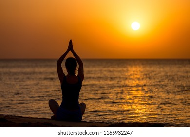 Back view of young woman practicing yoga on the beach, sitting on the seashore at sunset or sunrise in asana Sukhasana, hands above head, copy space