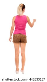 back view of young woman presses down on something. Isolated over white background. Rear view people collection. backside view of person. The girl in brown shorts and pink tank top is pointing to left