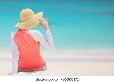 back view of young woman in rashguard and sunhat enjoying the perfect caribbean beach and protecting her skin from sun exposure during summer vacation, copyspace on the right