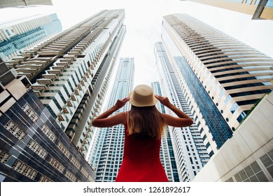 Back view of young woman in red summer dress holding with both hands straw hat looking up on skycrapers at downtown of modern city.