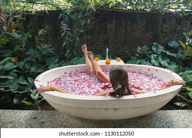 Back view young woman relaxing in Bath with petals in tropics. Time for yourself.