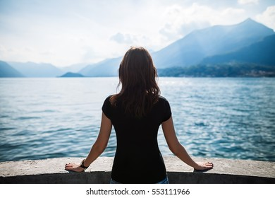Back view of young woman relaxing on terrace on lake Como, Italy. Travel concept