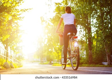 Back view of young woman riding on bike in the city park at summer sunset. Blurred background with copy space area for a text.