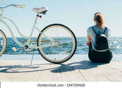 Back view young woman sitting on wooden embankment looking at sea near her shiny cruiser bicycle. Female wearing backpack resting after bike ride at sunny summer day.