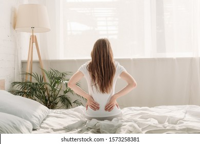 back view of young woman sitting on bed and suffering from back pain