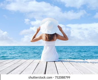 Back view of a young woman sitting on a pier.  Sea and sky background. Vacation and traveling concept.