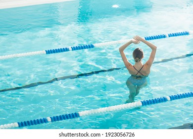 Back view of young woman standing with raised hands in swimming pool