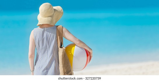 back view of young woman in sunhat holding beach ball at beautiful caribbean beach