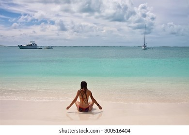 Back view of young woman with super long hair and in swimsuit sitting at white sand beach with turquoise sea water and few yachts at the horizon