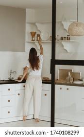 Zurück Ansicht von jungen Frauen, die Teller aus dem Regal in der Küche nehmen.