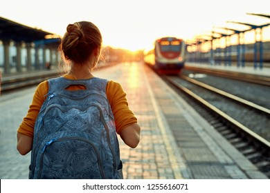 back view of a young woman traveler with small backpack on the railway stantion. woman waiting for train. Active and travel lifestyle concept