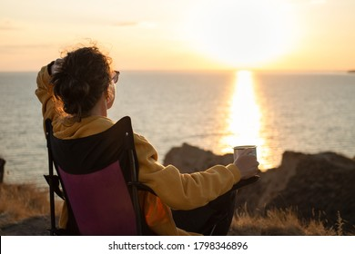 Back view of young woman traveler holding iron mug cup with tea or coffee,enjoying sunset scenery view of the sea landscape, sitting in touristic chair. Travel camping and adventure lifestyle concept