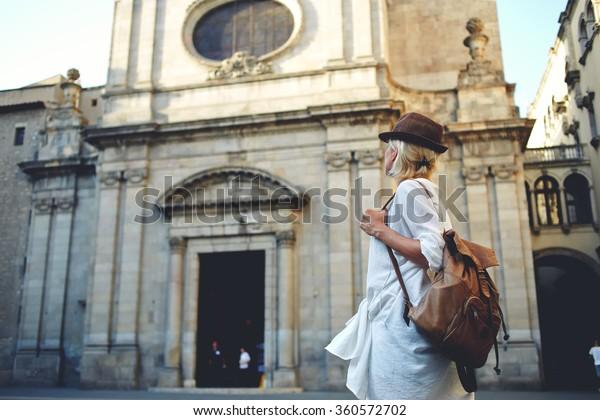 バックパックを背負った若い女性旅行者が、外国の街を見て回る様子を見ると、スタイリッシュな女性は、待望の夏休みに建築記念碑を調べる